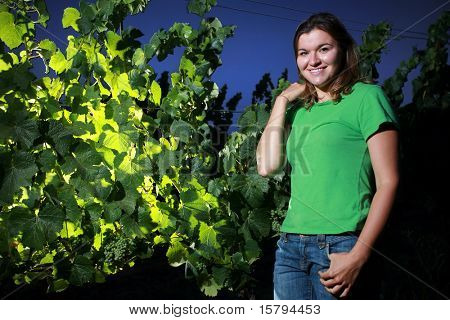 Young woman standing next to grape plant in Napa Valley, California, at dusk.