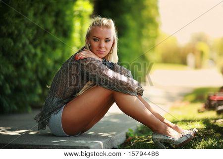 beautiful blonde Mädchen sitzen auf einer grünen Straße. shallow Dof.