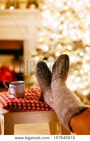 Cold winter night. Human resting by the Christmas tree with cup of tea. Closeup photo of feet in woolen socks in holiday decorated room. Cozy scene.
