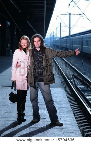 Young couple hitchhiking at train station
