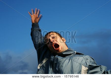 Crazy shouting young man outdoors over blue sky
