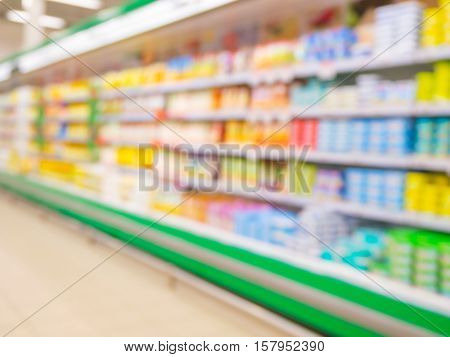 Defocused blur of supermarket shelves with dairy products. Blur background with bokeh. Defocused image
