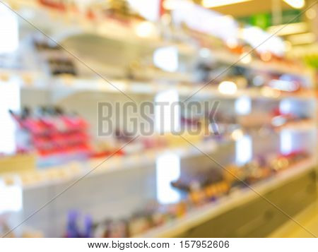 Abstract blurred supermarket aisle with colorful makeup cosmetic goods shelves as background