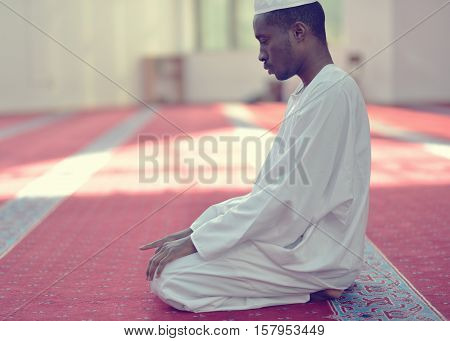 African Muslim Man Making Traditional Praying To God While Wearing A Traditional Cap Dishdasha