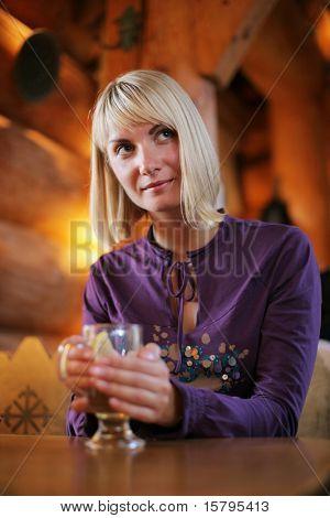 Beautiful young woman enjoying a drink. Shallow DOF.