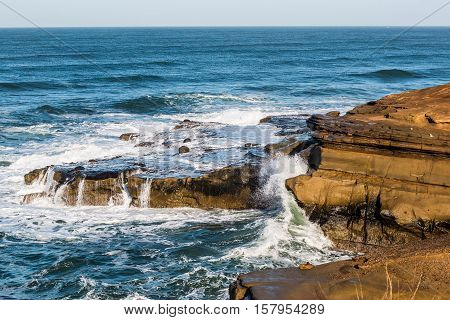 Waves crashing over rock formations at Sunset Cliffs in San Diego, California.