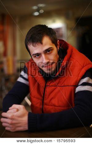 Retrato de un joven en chaleco deportivo rojo. DOF bajo, foco en los ojos.