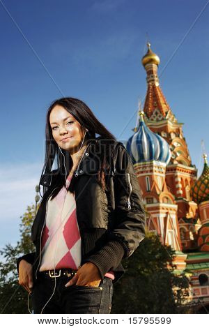 Beautiful young woman next to Saint Basil's Cathedral in Red Square, Moscow, Russia.