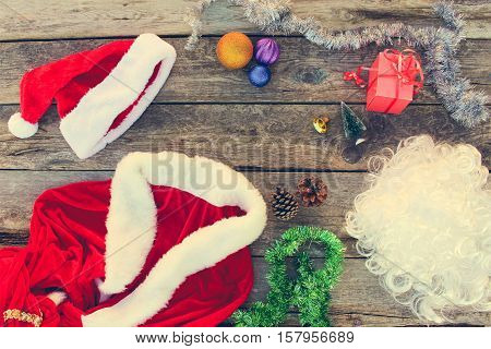 Santa Claus suit, small tree, pinecone, Christmas balls, garland, gift on wooden background. Top view. Toned image.