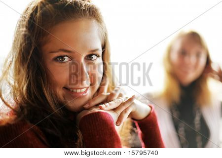 Two beautiful young women in restaurant with cup of tea