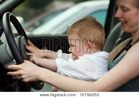 Little boy at drivers seat together with mother. Shallow DOF.