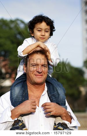 Father with son sitting on his shoulders. Shallow DOF.