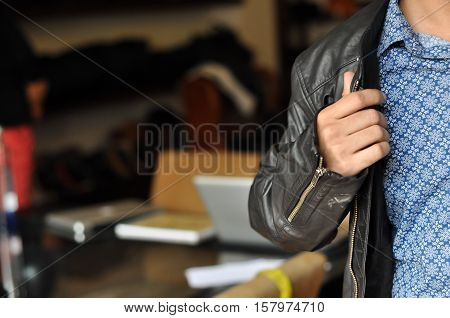 Partial close up of a young buyer trying jacket at a clothing store. Sale, shopping, fashion, style and people concept without face. Young man tying leather jacket at the mall or clothing store