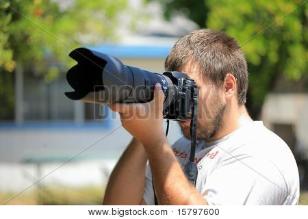 Photographer with professional camera and telephoto lens shooting outdoors. Shallow DOF.