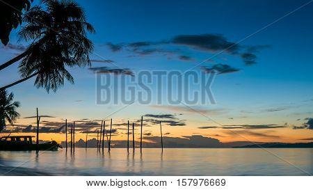 Sunset on Kri Island. Boats under Palmtrees. Raja Ampat, Indonesia. West Papua