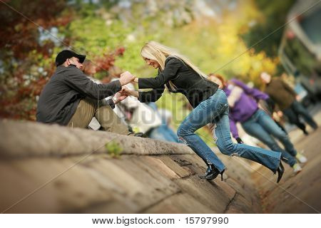 Man helping woman to climb wall in park. Shallow DOF.