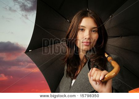 Beautiful Asian woman with umbrella over dramaric sunset sky background.