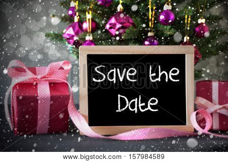 Chalkboard With English Text Save The Date. Christmas Tree With Rose Quartz Balls, Snowflakes And Bokeh Effect. Gifts Or Presents In The Front Of Cement Background.