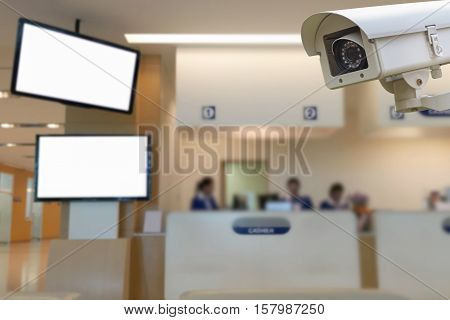 The CCTV security camera operating in center cashier hospital blur background.