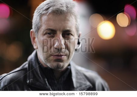 Portrait of mid-adult man in night city. Closeup, shallow DOF.