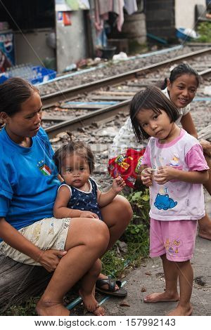 Bangkok , Thailand - july 26, 2005:  A mother and her children living along the railroad tracks. There are an estimated 7.3 million people that are considered to be in poverty in Bangkok, Thailand.