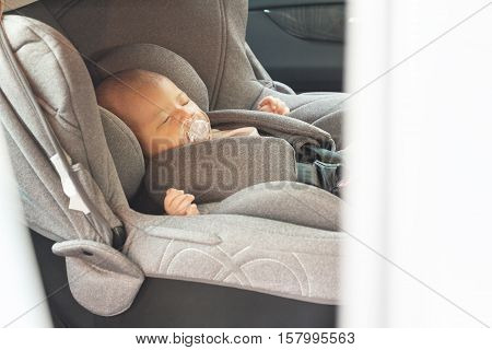 Asian cute newborn baby sleeping in modern car seat. Child new born traveling safety on the road. Safe way to travel fastened seat belts in a vehicle with young kids. Trip with an infant.