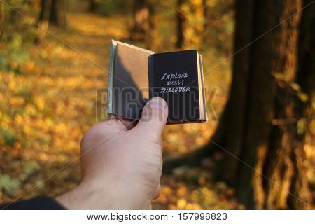 Hand holding a book with the inscription Explore Dream Discover.