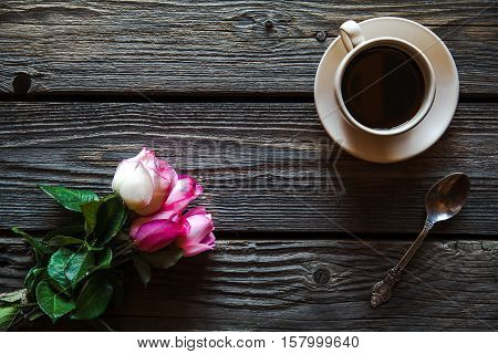 cup of coffee with red rose and and copy space on wood background. breakfast on Mothers day Women's day valentine's day or birth day. hot drink flowers