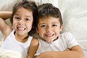 foto of brother sister  - Cute brother and sister laying in bed - JPG