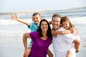 stock photo of family fun  - Happy loving family playing on the beach - JPG