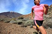 Running. Woman Cross country trail runner running on the mountain / volcano Teide on Tenerife. Beaut