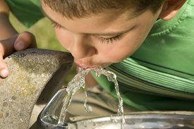 foto of drinking water  - Little boy drinking water from a fountain - JPG