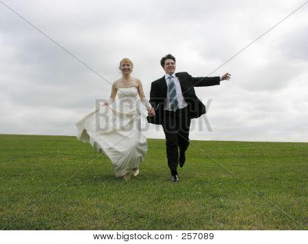 Bride And Groom Running On Meadow