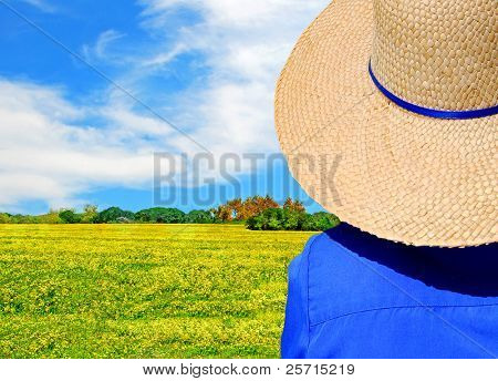 Hatted Woman Looking at Beautiful Meadow