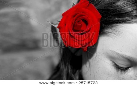 Young Girl with Beautiful Red Rose Behind Ear Looking Downward
