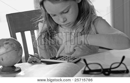 Young Studious Girl Using Calculator During Homework