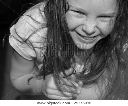 Freckle Faced Girl With Scrunched Up Nose While Bending Over Laughing