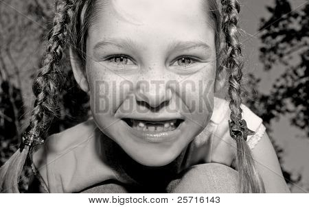 Cute Freckle Face Girl in Braid Pigtails with Missing Front Teeth