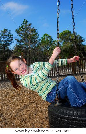 Young Girl in Ponytails Missing front Teeth on Tire Swing