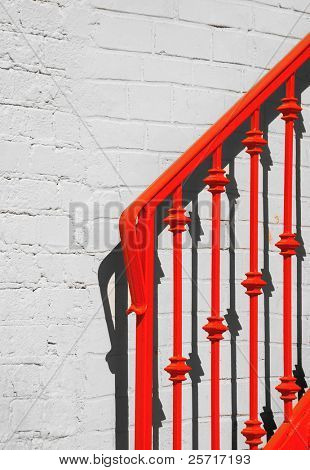 Red hand railing to stairs casting shadow on brick wall