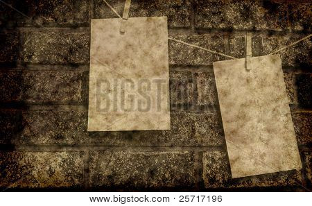 Two pieces of notepaper on clothesline against brick wall with grunge overlay