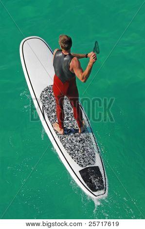 Muscular Male auf Surfbrett mit Paddel