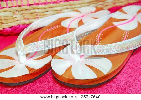 Pretty flip flop sandals with sequins on towel next to beach bag