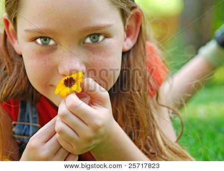 Girl Laying on Grass Holding Daisy