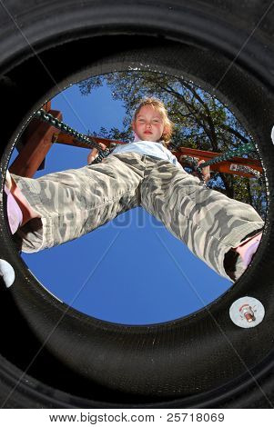 Young tomboy girl on tire swing