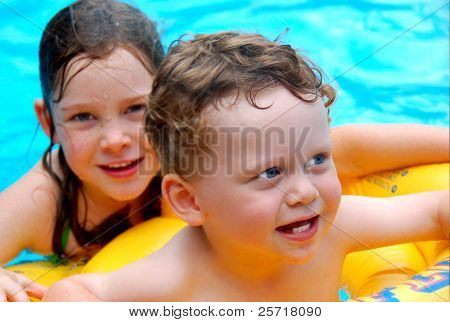 Cute Young Boy in Pool with Sister Looking On