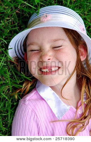 Young girl missing front teeth laying on grass and smiling