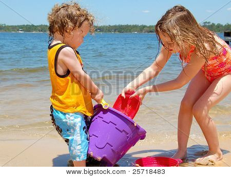 Cute young boy and girl playing in sand on seashore