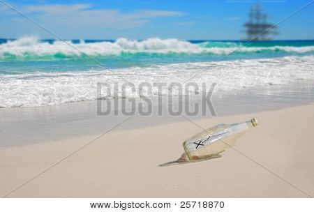 Beautiful beach with mysterious map in bottle with pirate ship in distance