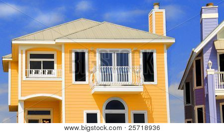Brightly colored tropical homes under blue sky